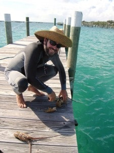 Captain David Ryan shows off snorkel-caught lobsters on Spanish Cay, Bahamas