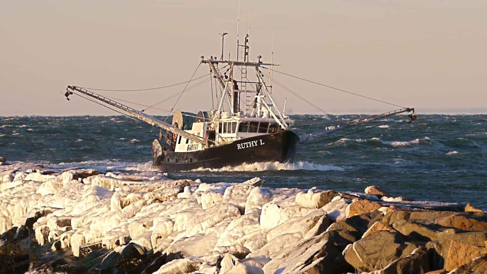 The trawler Ruthy L coming into Montauk Harbor on a bitterly cold January day. Ice on the jetty in the foreground.