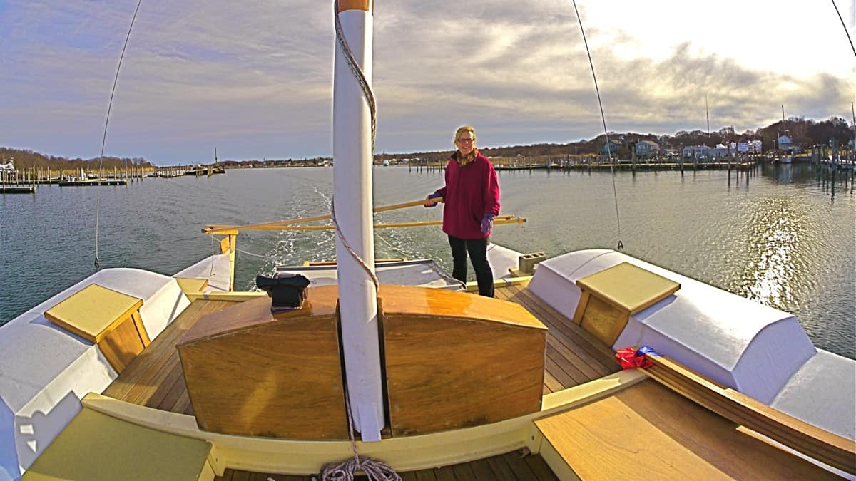 After a day of fabrication dock-side, Jennifer Richards take the helm of the charter sailing catamaran MON TIKI for a little sight-seeing around Montauk Harbor and Lake Montauk, March 2013, Montauk, NY, photo by Sailing Montauk