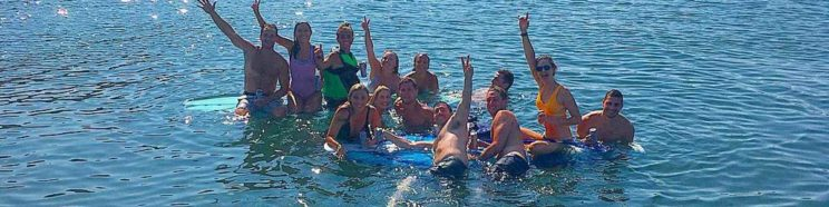 Friends celebrate in the water on a Mon Tiki sail and swim outing